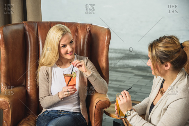 Positive girlfriends enjoying cocktails in armchairs