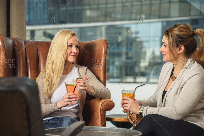 Adult women with cocktails resting near window