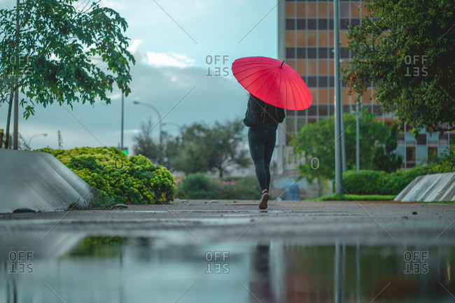 Woman with red umbrella walking behind a puddle in Palma, Spain