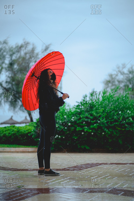 Woman with a mask holding a red umbrella looks up while raining