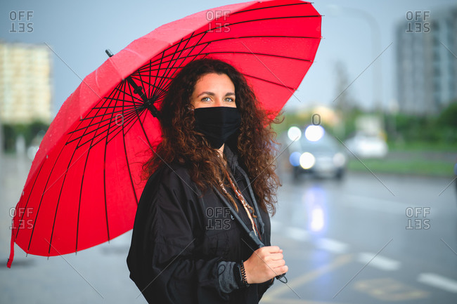 Portrait of a woman with a mask and a red umbrella looking at camera
