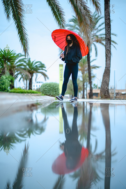 Woman with a mask and a red umbrella reflected on a puddle