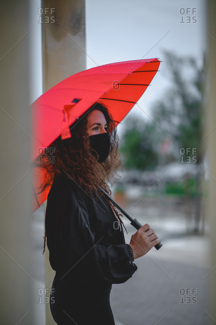 Woman with a mask and a red umbrella seen between two columns