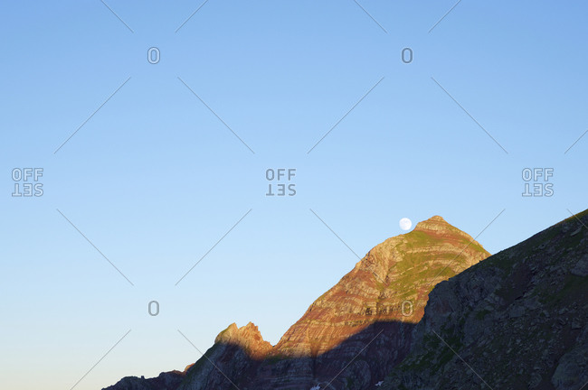 Moon and peak at sunset, Tena Valley in Huesca Province, Pyrenees in Spain.