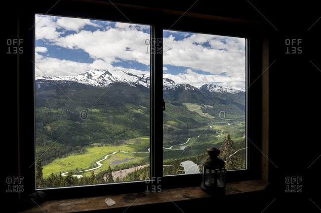 Snowy mountain ridge and green valley with curvy road located behind window of wooden cabin with retro lantern in highlands of British Columbia, Canada