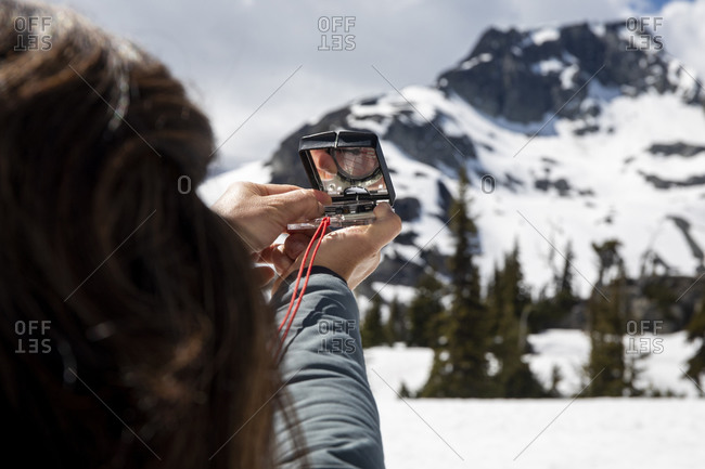 Unrecognizable female hiker using compass for navigation during trip through snowy mountains on cloudy day
