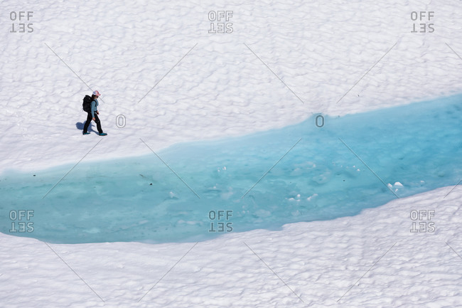 Drone view of unrecognizable female hiker walking along melting lake with clear blue water during vacation in British Columbia