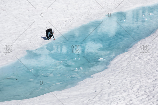 Drone view of unrecognizable female hiker resting and putting hand in melting lake with clear blue water during vacation in British Columbia