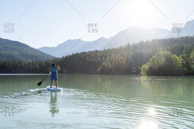 Barefoot woman in dress and life vest riding paddle board on calm lake water on sunny summer day in mountains in British Columbia, Canada