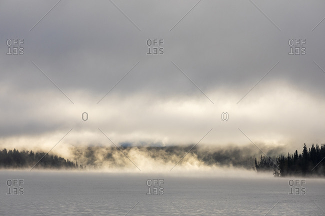 Thick mist over calm lake water and overcast sky during sunrise