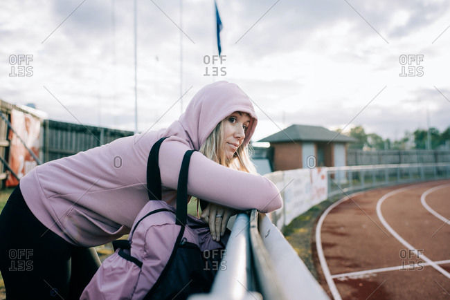 Woman stands by a running track looking thoughtful