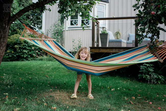 Young girl standing by a hammock smiling have fun in a garden at home