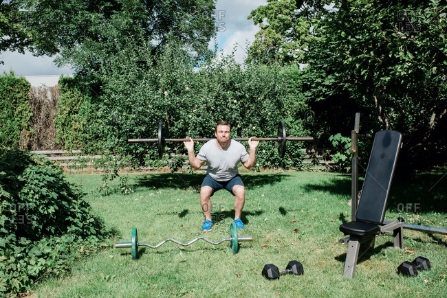 Man working out at home in the garden with his home gym equipment