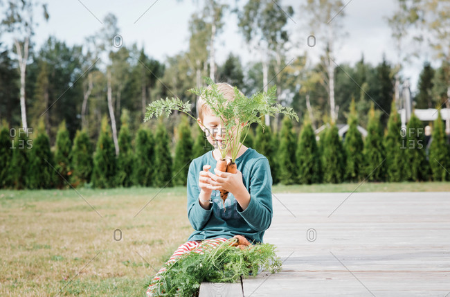 Young boy sits in his garden smiling at his homegrown carrots