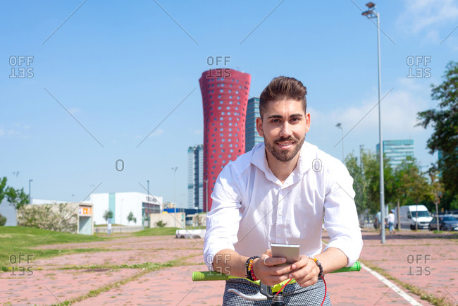 Outdoor portrait of handsome young man with mobile phone and fixed gear bicycle in the street.