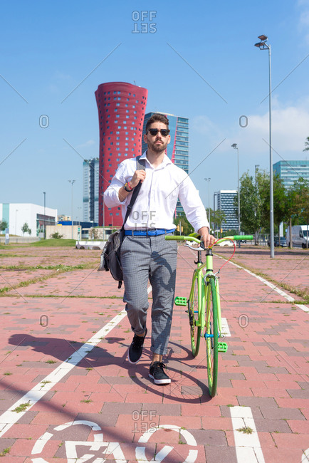 Bearded man in sunglasses walking with bike by bicycle track outdoors