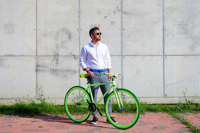 Young bearded man with sunglasses standing with bike outdoors