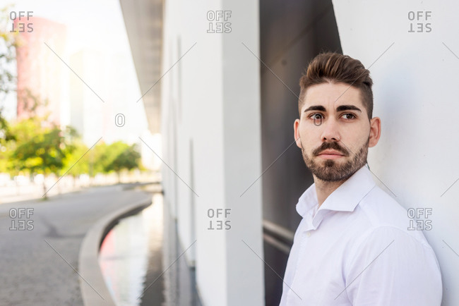 Portrait of a bearded man leaning on white wall looking aside
