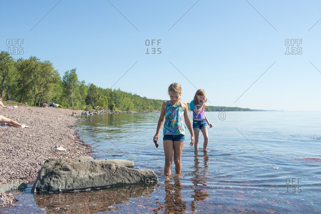 Two Young Girls Exploring Rocky Shoreline