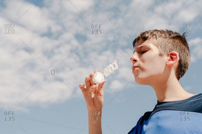 Young white boy blowing a soap bubble outdoors with sky at background