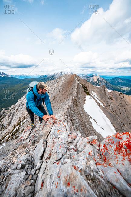 Mountain Runner Scrambling up Mountain Ridge in Canadian Rockies