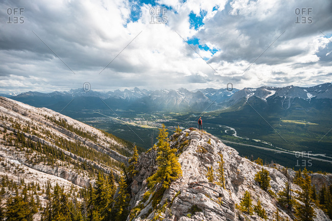 Hiker Standing on Mountain Ridge Above City of Canmore Alberta
