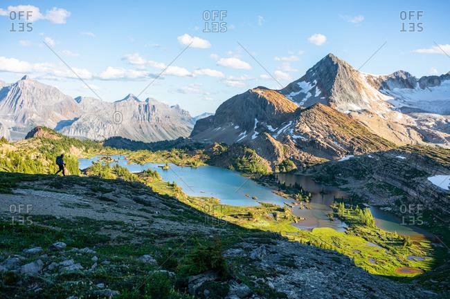Silhouetted Hiker Walks Down Ridge Towards Limestone Lakes in Rockies