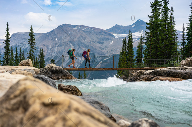 Hikers Crossing Glacial River Over Twin Falls Along the Whaleback