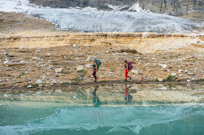 Glacier Reflects in Alpine Lake While Walking Alongside Lake's Shores
