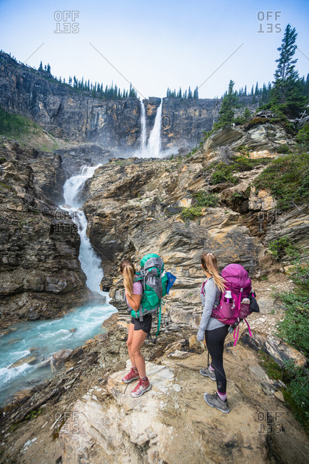 Two Hikers Admiring Twin Falls Waterfall In Yoho National Park