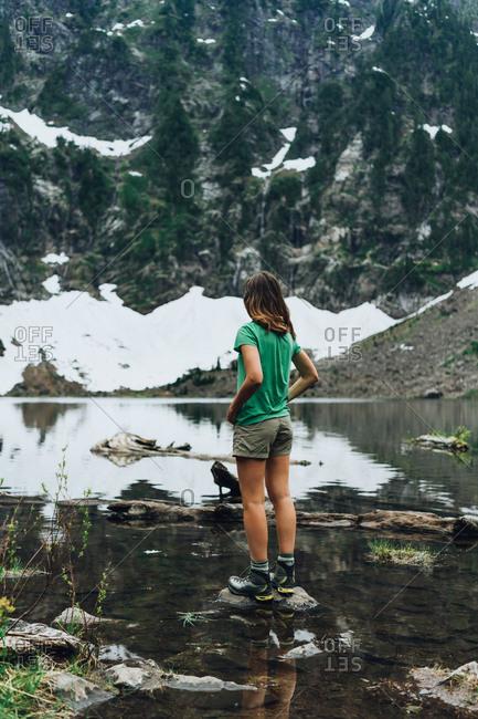 Hiker admiring waterfalls at the mountain lake in Washington