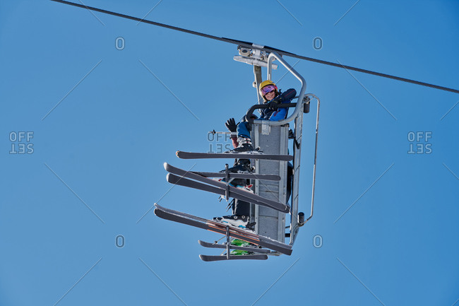 Skiers on a chairlift looking down with a blue background