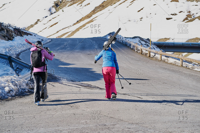 two skiers carry their skis on their shoulders along the road