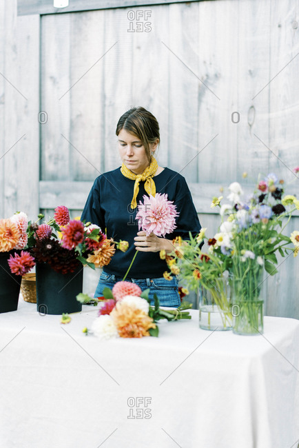 Photo of a woman arranging bouquets with her self grown flowers