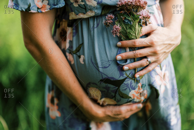 A beautiful pregnant woman holding her growing belly