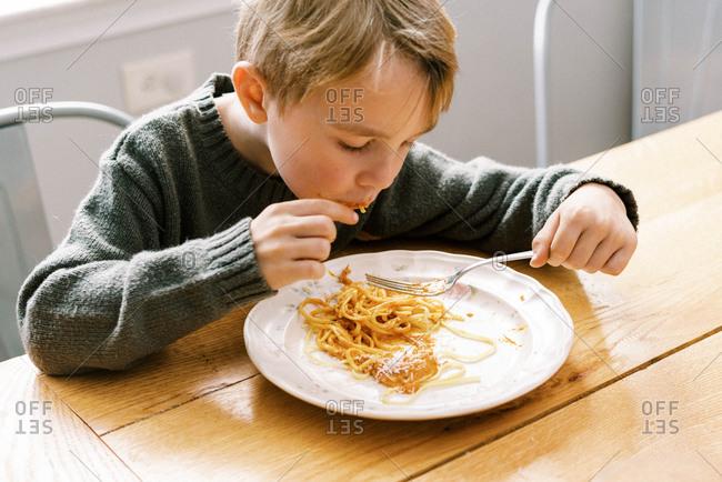 A little boy enjoying his homemade tomato sauce from garden tomatoes
