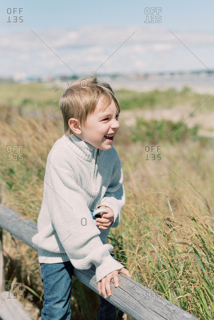 Little boy sitting on a fence by the dunes