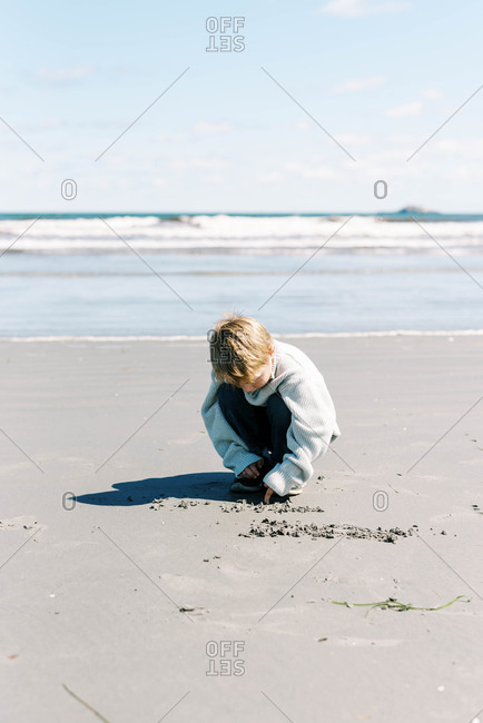 Little boy drawing in the sand on a beach in Massachusetts