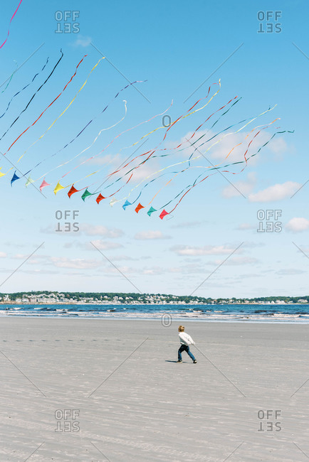 A boy chasing a large kite flying past him on a New England beach