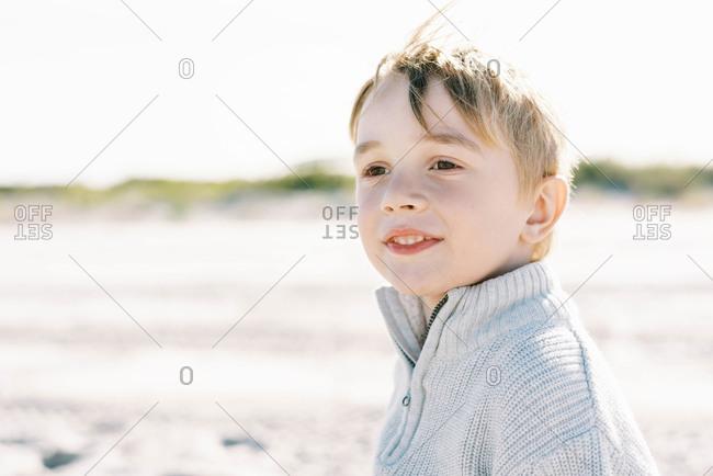 Smiling little boy enjoying a windy beach day in New England