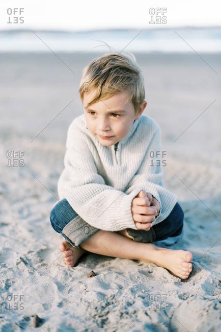 Little boy sitting in the sand on a windy beach looking toward the sun