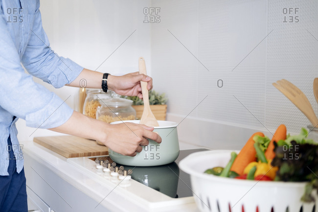 Man cooking healthy food in the loft kitchen at home