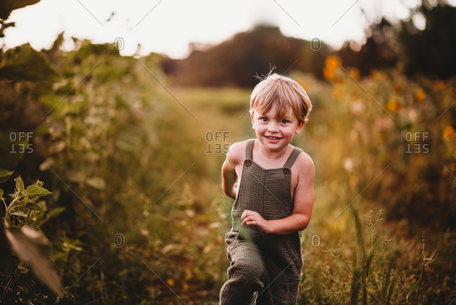 Happy boy running in a flower field wearing green dungarees