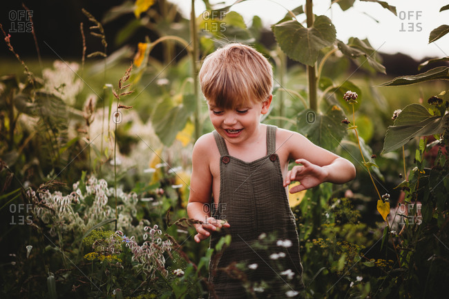 Close up of a smiling child walking in a field wearing dungarees