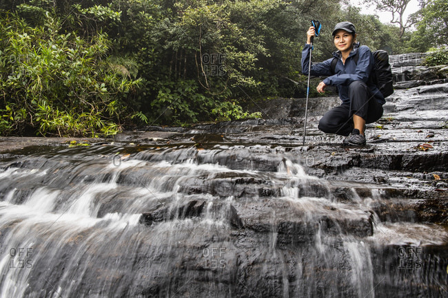 Woman exploring small waterfall in the mist of Sri Lankan highlands