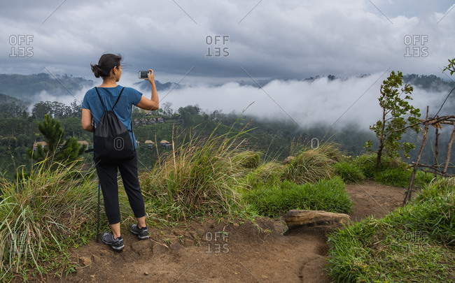 Woman taking a picture at the top of Adam's Peak close to Ella