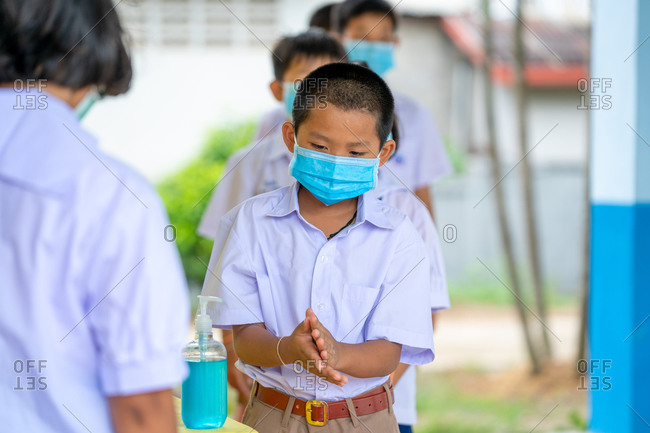Elementary school students wearing hygienic mask and using hand sanitizer