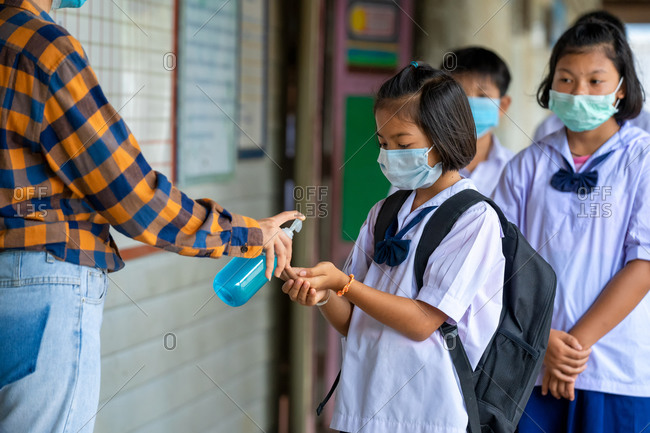 Teacher and elementary children with face mask are disinfecting their hands
