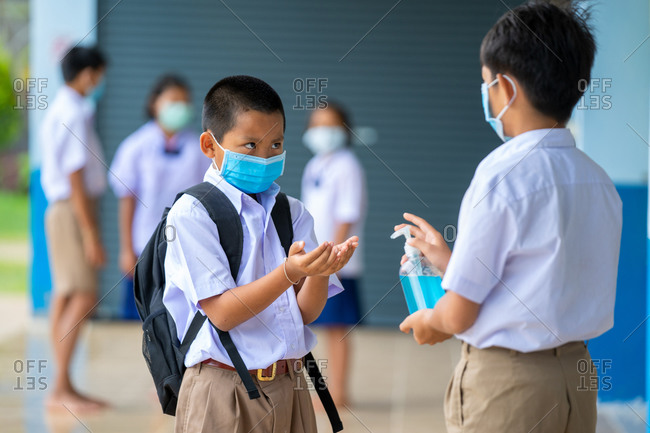 Asia elementary children spraying classmate's hands with disinfectant