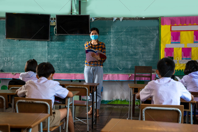 Students and her teacher wearing protective face masks in classroom